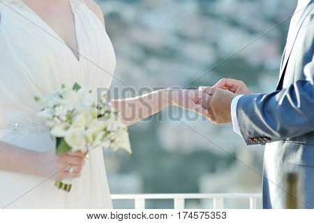 Groom putting wedding ring on bride's finger in wedding day