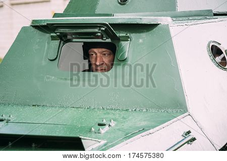 Pribor, Belarus - April 23, 2016: Re-enactor Dressed As Russian Soviet Crew Member Soldier Of World War II Looking Through Inspection Hatch Of The At Armoured Soviet Scout Car BA-64