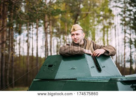 Pribor, Belarus - April 23, 2016: Young Re-enactor Dressed As Russian Soviet Soldier Of World War II Sitting In Armoured Soviet Scout Car BA-64 In Forest.