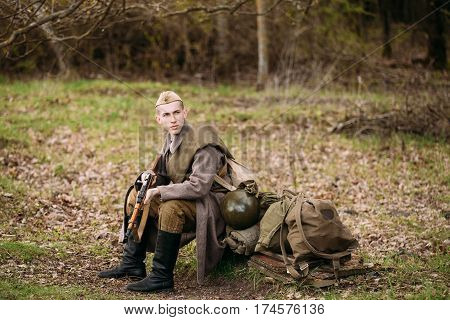 Pribor, Belarus - April 23, 2016: Young Man Re-enactor Dressed As Russian Soviet Red Army Infantry Soldier Of World War II Sit Near Military Equipment With Mosin-Nagant Rifle In Hands In Forest