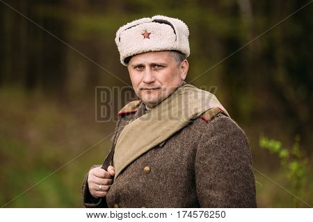 Pribor, Belarus - April 23, 2016: Close up portrait of Re-enactor Dressed As Russian Soviet Red Army Infantry Soldier Of World War II And Looking at Camera In Forest