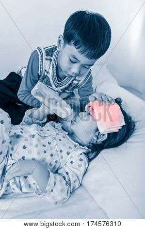 Asian girl have a fever resting and suck up milk at hospital room kindly brother keep vigil over a sick of closely. Color increase blue skin and red spot indicating of fever. Concept of a nice family