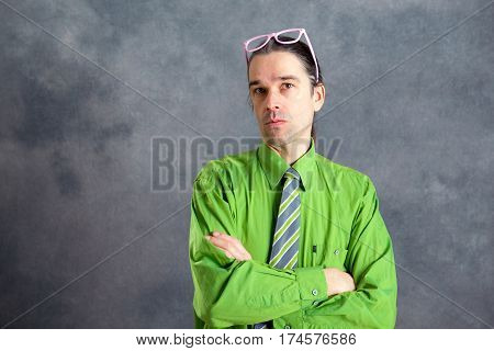 Man In Green Shirt Pink Glasses On Head Looking Skeptical
