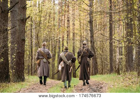 Three Re-enactors Dressed As Soviet Russian Red Army Infantry Soldiers Of World War II Marching Along Forest Road At Spring Season.