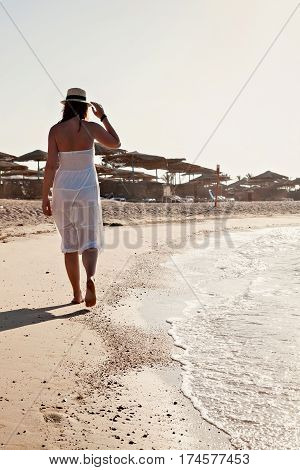 Young Woman In White Dress Walking Along The Seashore