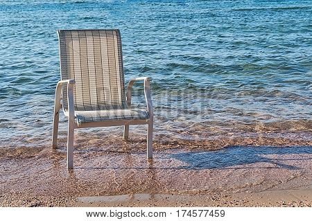 A chair stood in the sea water near the coast.