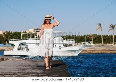 Young woman in white clothes posing and goes on the pier with yachts.