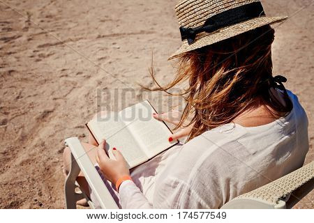 Young Adult Woman With A Hat On The Beach Reading A Book