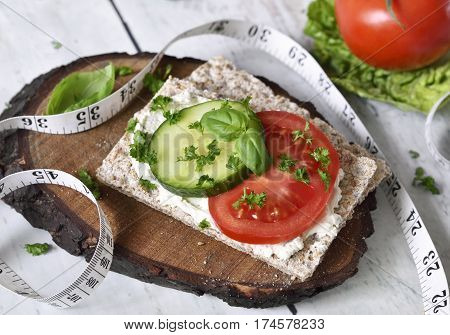 Healthy eating or dieting scene with crisp bread and fresh tomatoes and cucumber. Tape measure and wooden table.