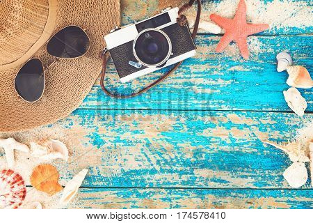 Summer background - The concept of leisure travel in the summer on a tropical beach seaside. retro camera with starfish shells coral on wood table background. vintage color tone styles.