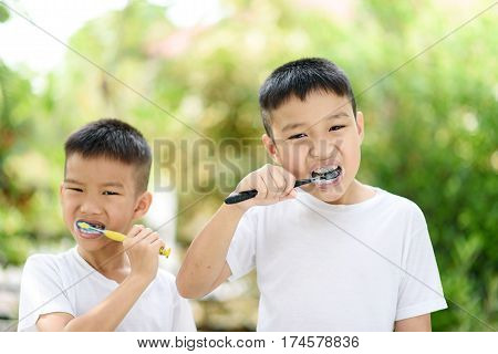 Boy Brushing Teeth In The Garden