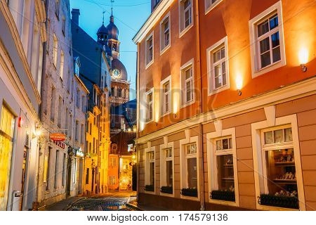 Riga, Latvia - July 1, 2016: View Of Deserted Narrow Cobbled Kramu Street Of Old Town In Bright Evening Illumination With Ancient Architecture Leading To Dome Cathedral Under Summer Blue Sky.