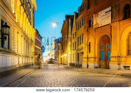 Riga, Latvia - July 1, 2016: Evening View Of Pils Street With Ancient Architecture In Bright Warm Yellow Illumination Under Summer Blue Sky. Our Lady Of Sorrows Or Virgin Of Anguish Church In Distance