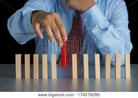 Businessman Hand Pick One Of Wood Block From Many Wood Block In Row, Metaphor To Business Concept In