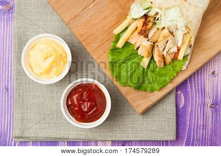 Arabic shawarma on wooden board and two white cups with ketchup and cheese on purple wooden table