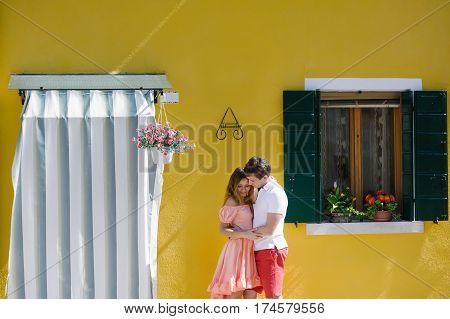 Tender couple near a yellow house in Burano island Venice Italy Europe