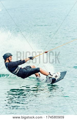 Woman stunt on wakeboard on lake, color image, blue background