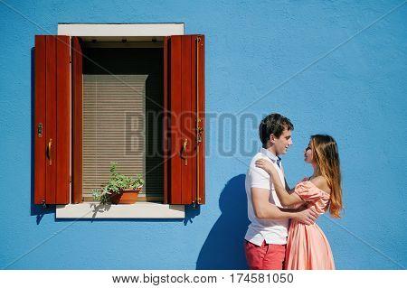 Happy couple near a light blue house in Burano island Venice Italy Europe