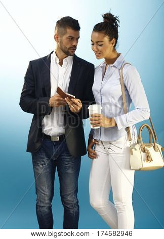 Young couple looking at mobilephone over blue background.