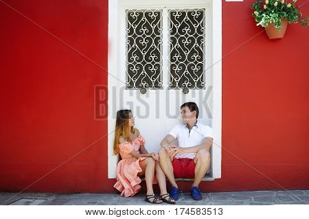 Young couple on vacation relaxing near a red house in Burano Venice Italy Europe