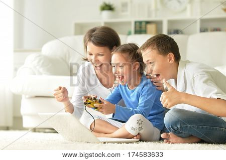 family playing computer games, mother with kids