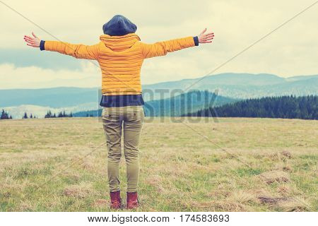Girl with arms wide open enjoying in nature.