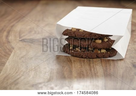 homemade chocolate cookies with chocolate chips and hazelnuts in paper bag on table, shallow focus
