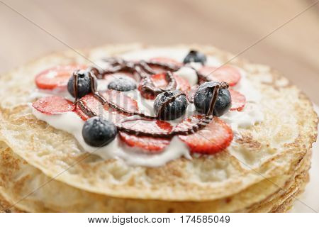 fresh blinis or crepes with fresh berries and cream decorated with chocolate sauce, closeup photo