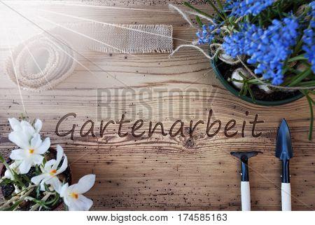 German Text Gartenarbeit Means Gardening. Sunny Spring Flowers Like Grape Hyacinth And Crocus. Gardening Tools Like Rake And Shovel. Hemp Fabric Ribbon. Aged Wooden Background