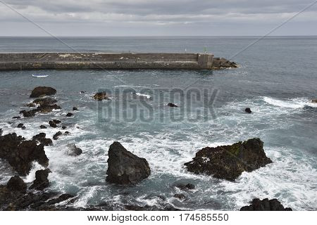 Waves and rocks in foreground and a pir in background picture from Puerto de la Ceus Tenerife Spain.