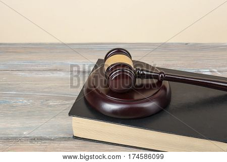 Book with wooden judges gavel on wooden background in a courtroom office.Judgement concept.Copy space for text.