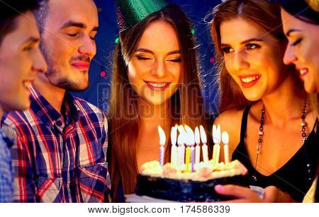 Happy friends birthday celebrating food with candle celebration cakes. People wear in hat party looking at burning candles. Women and men have fun.