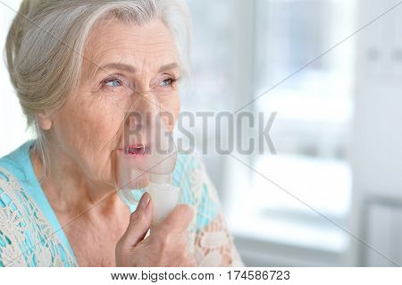 Portrait of a sick elderly woman making inhalation