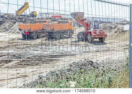 View through a fence wire on big loader until is filling a dump truck with soil at construction site project in progress.