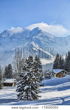 Beautirul winter landscape with wooden chalets and the top of Monta Blanc covered by windy clouds in the background.