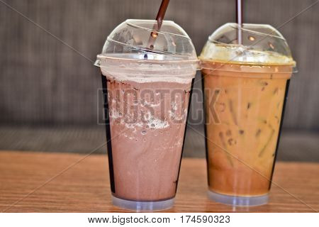 Iced milk tea and iced cocoa in plastic glass put on a wooden table