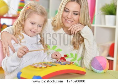 mother with little daughter playing on instrument