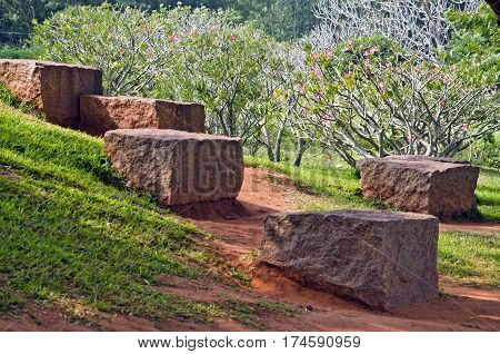 Natural stone granite cubes in park and blossoming bushes in Auroville India