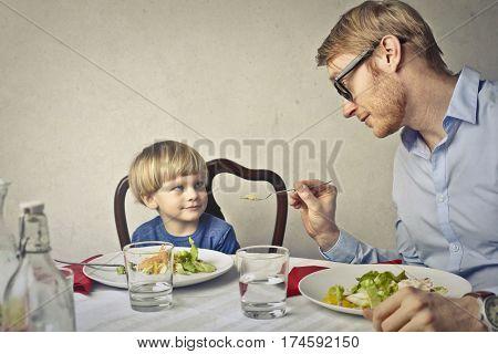 Dad feeding his little son