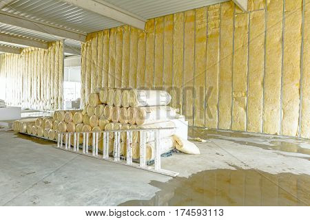 Stack of thermal insulation material in roll is wrapped with cellophane foil. Used wooden ladder to complete dividing wall