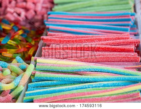 Mixed colorful bonbon close up. Background with various colorful candy. Long chewy jelly sweet candies.