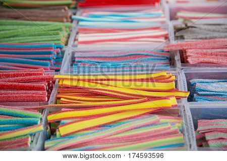Mixed colorful bonbons close up. Background with various colorful candies. Long chewy jelly sweet candies.
