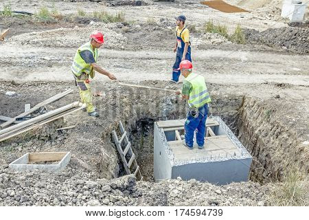 Zrenjanin Vojvodina Serbia - June 29 2015: Construction workers are preparing wooden mold for concrete pouring slab on utility hole.