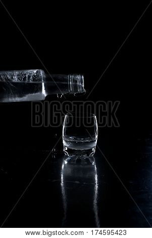Close-up view of bottle Vodka poured into a glass on black background