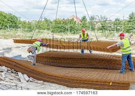 Zrenjanin Vojvodina Serbia - June 29 2015: Team of riggers assist mobile crane to unload reinforcing mesh on pile. Workers are helping in manage the cargo.