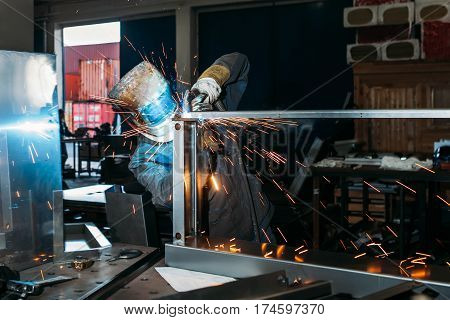 sparks while welder uses torch to welding industry