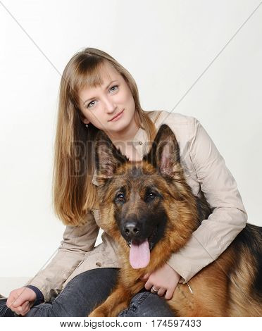 Happy Young Woman hugs beautiful fluffy German Shepherd dog against white background