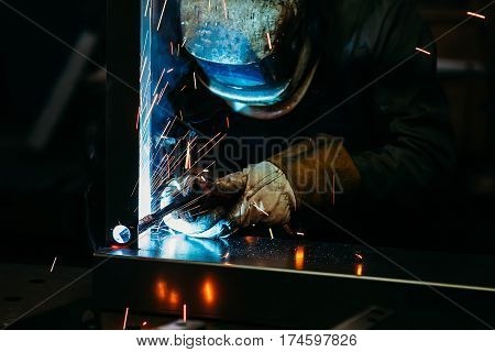 sparks while welder uses torch to welding in gloves
