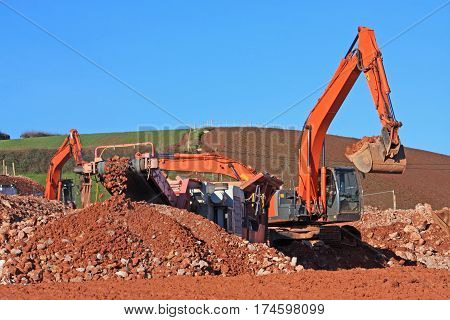 Digger loading a stone crusher on a construction site