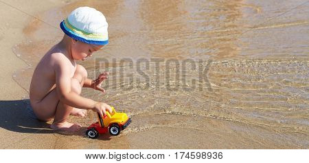 Little Boy Plays In The Water In The Sea